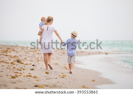 Young mother in white dress walking with her two little boys along the ocean beach. Woman with children enjoying vacation by the sea. Motherhood. - stock photo
