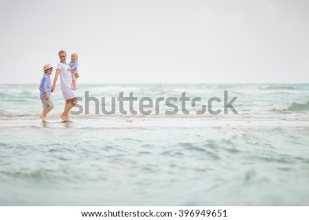 Young mother in white dress walking with her two little boys along the ocean beach. Woman with children enjoying vacation by the sea. Motherhood. Beautiful family. Water background.  - stock photo