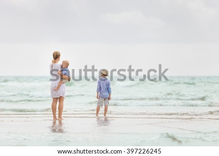 Young mother in white dress walking with her two little boys along the ocean beach. Woman with children enjoying vacation by the sea. Motherhood. Beautiful family.Water background. copy space.