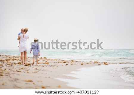 Young mother in white dress walking with her two little boys along the ocean beach. Woman with children enjoying vacation by the sea. Motherhood. Beautiful family. - stock photo