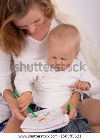 Young mother is drawing with her son indoors