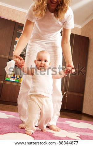 Young mother is helping her daughter to make first steps - stock photo