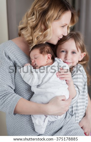 Young mother is holding her newborn baby and hugging her children - stock photo