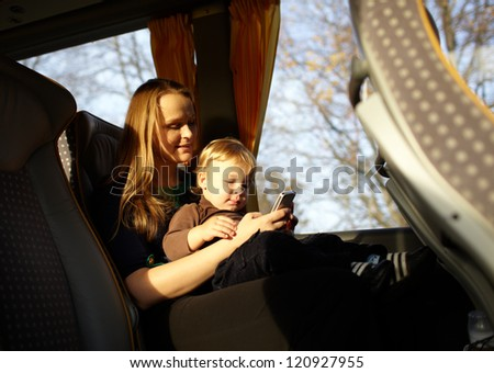 Young mother is playing games on the phone with her son, while travelling by bus. Beautiful natural light. - stock photo