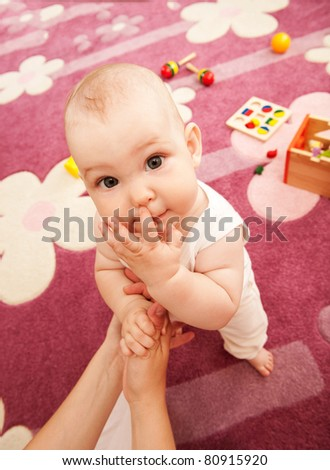 Young mother is playing with her baby n playroom - stock photo