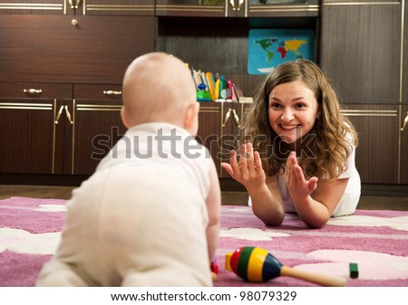 Young mother is playing with her baby n playroom