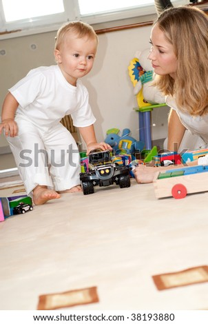 Young mother is playing with her little son. Shoot from low view - stock photo