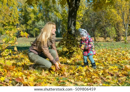 Young mother is playing with little daughter in the autumn park, they throw each other fallen leaves. Sunny autumn day.