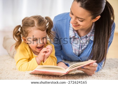 Young mother is reading a book to her cute daughter. - stock photo