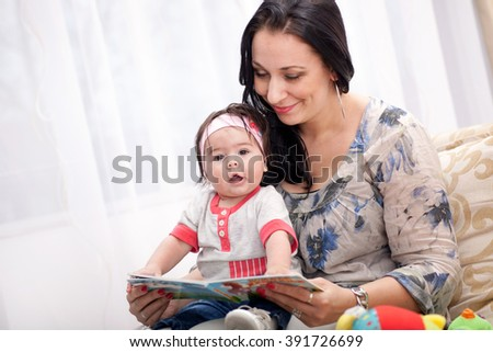 Young mother is reading a book to her cute daughter
