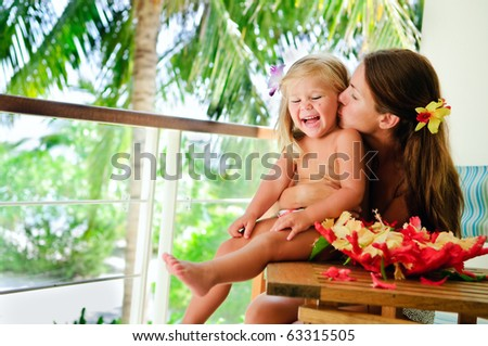 young mother kiss her little daughter at tropical garden background