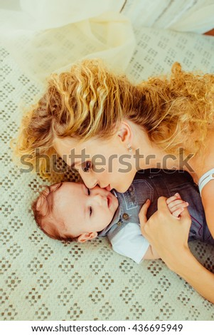 young  mother kisses her baby  on the cheek - stock photo