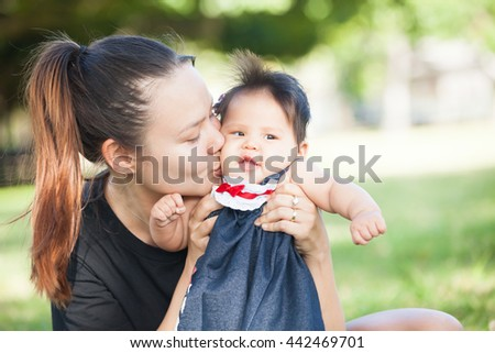 Young mother kisses her cute baby on the cheek - stock photo