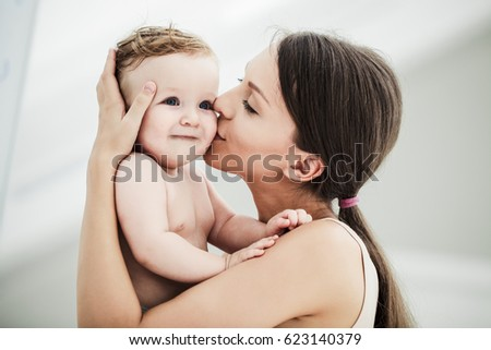 Young mother kissing her adorable baby boy.