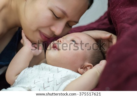 Young mother kissing her little baby - stock photo