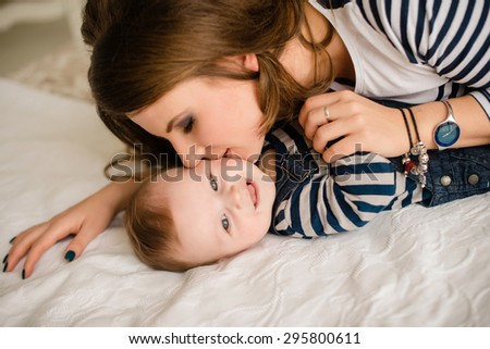 Young mother kissing her little newborn baby - stock photo