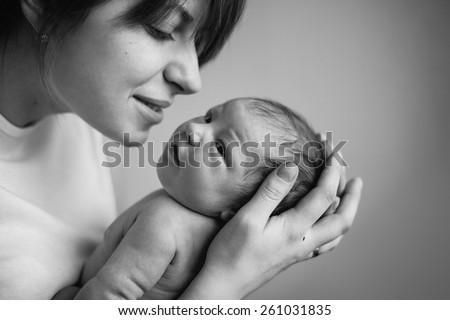 Young mother kissing her little newborn baby. black and white - stock photo