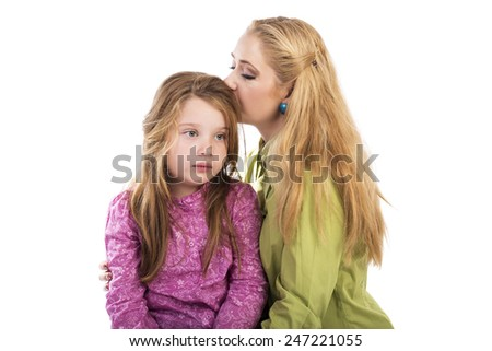 Young mother kissing  her lovely daughter over white  background - stock photo
