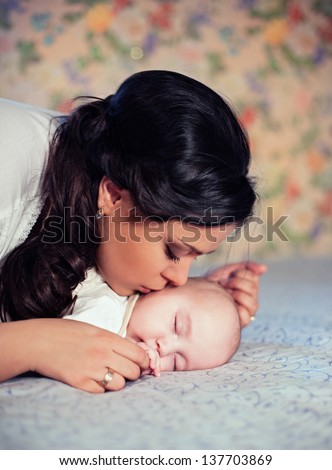 Young mother kissing her small sleeping newborn baby - stock photo