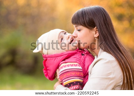 Young mother kissing kid girl outdoors in autumn park - stock photo