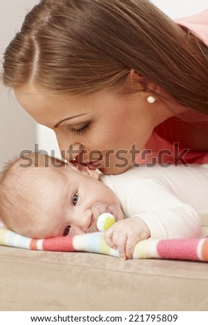 Young mother kissing lying baby.