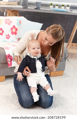 Young mother kneeling on floor at home with little baby girl on lap. - stock photo