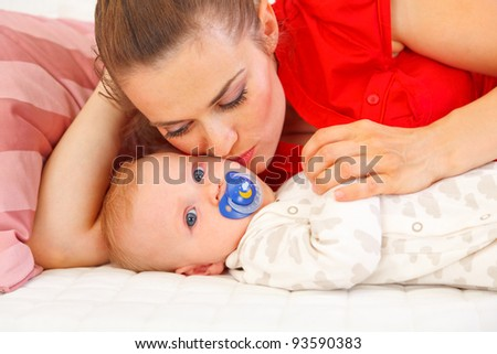 Young mother laying on couch and kissing baby