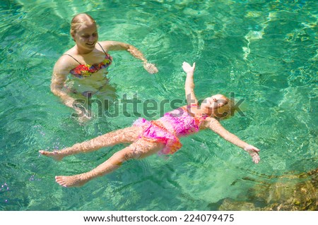 Young mother learn adorable daughter to relax in crystal clear laguna on tropical island - stock photo