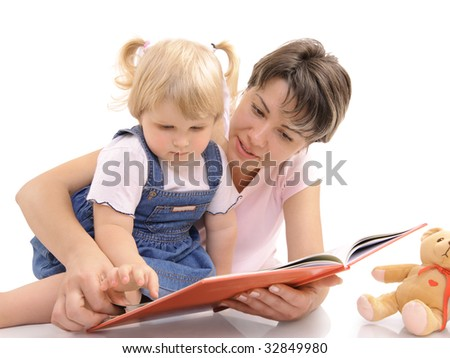 Young mother looking at books together with her little daughter - stock photo