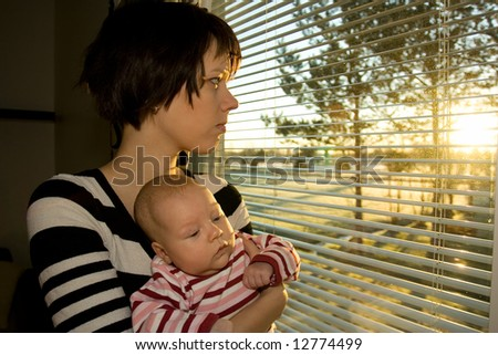 Young mother looking out from the window with her baby - stock photo