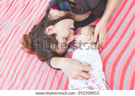 Young mother lying down and embracing her little daughter. They are at park, the mother is smiling and cuddling her daughter. Vintage filter added. - stock photo