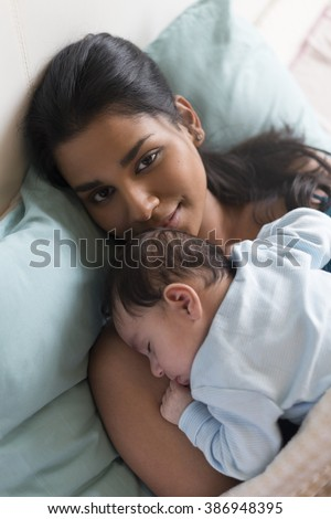 Young mother lying in bed with her baby son sleeping on her chest. She is smiling at the camera. - stock photo