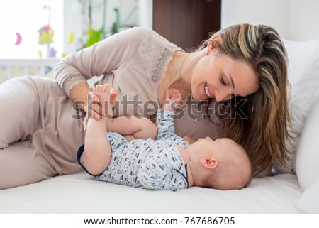 Young mother, lying in bed with her newborn baby boy, playing and interacting together. Family happiness concept. Back light fron the window behind