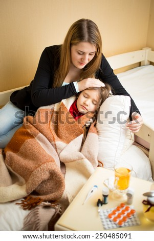 Young mother lying next to sick daughter in bed - stock photo