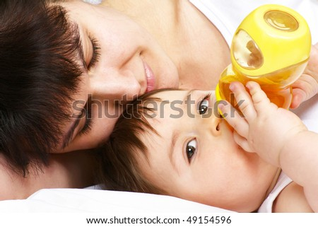 young mother lying on bed with her baby and feeding him with a bottle - stock photo