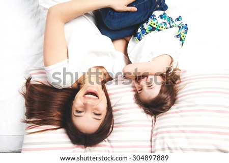Young mother lying on bed with her little daughter and laughing - stock photo