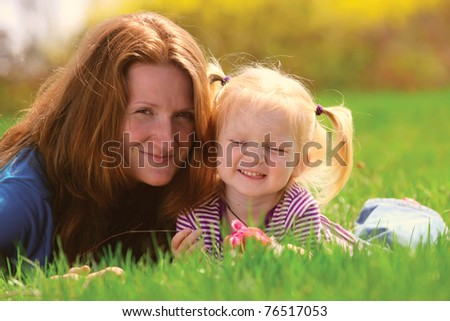 young mother lying with child girl on a grass at the park - stock photo