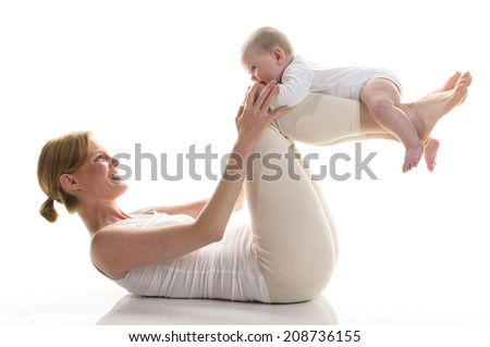 Young mother makes with her 6 month old daughter Rueckbildungsgymnastik, isolated against white background. Mama is down and has her baby lying on their lower legs. - stock photo