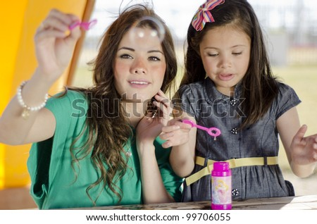 Young mother making bubbles with daughter