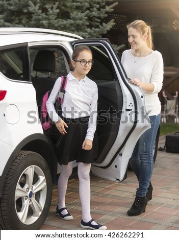Young mother opening car door to her daughter after trip from school