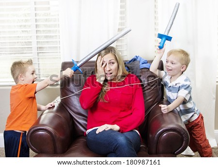 Young Mother overwhelmed by her kids - stock photo