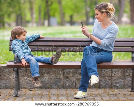 Young mother photographing her cute little son posing on a park bench - stock photo