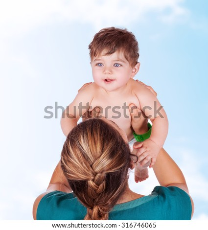 Young mother play with baby, lifting up her precious adorable son in the sky, having fun together outdoors, happy family life - stock photo
