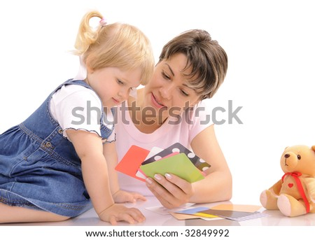 Young mother playing together with her little daughter - stock photo