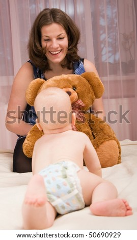 Young mother playing with baby boy in bed - stock photo