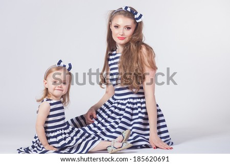 Young mother playing with daughter - stock photo