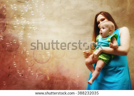Young Mother Playing with Her Baby and Soap Bubbles. Baby is Surprised. Selective Focus, Blurred Effect. Image Toned. - stock photo