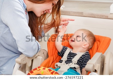young mother playing with her baby at home - stock photo