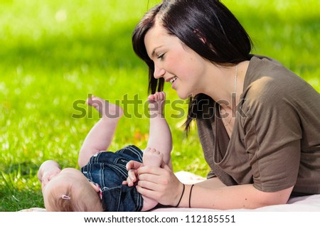 Young mother playing with her baby daughter on grass. - stock photo