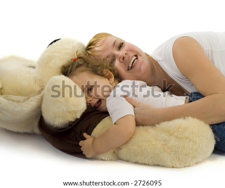 Young mother playing with her baby girl and a giant plush dog - stock photo